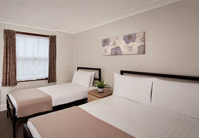 single and double bed in hotel room