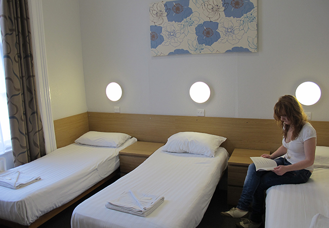 triple bedroom and woman at budget hotel